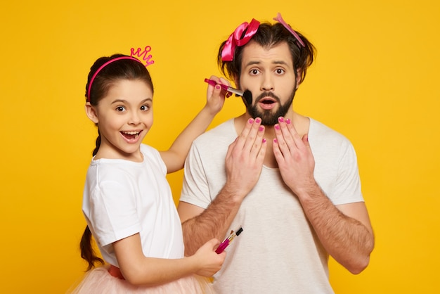 Little smiling girl cleans dads face with brush. Premium Photo