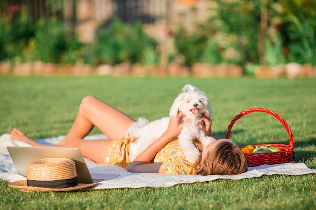 Маленькая усмехаясь девушка играя с щенком в парке Premium Фотографии