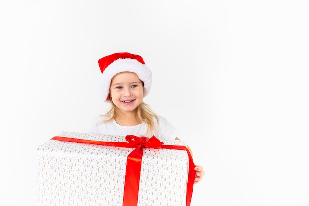 Little smiling girl in santa helper hat holding white gift with red ribbon on white Premium Photo