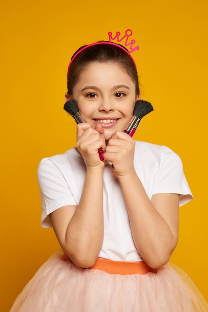 Little smiling girl stands with makeup brushes Premium Photo