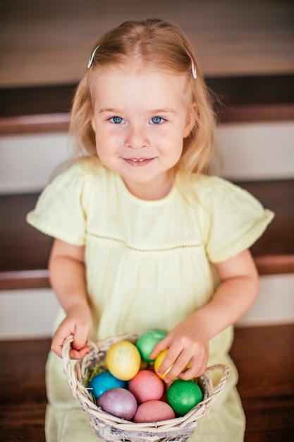 塗装済み完成品卵とバスケットを保持し、イースター、自宅の階段に座って少し笑みを浮かべてirl Premium写真