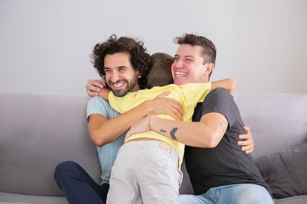 Piccolo figlio che abbraccia due padri belli felici a casa. colpo medio. famiglia felice e concetto di genitorialità Foto Gratuite