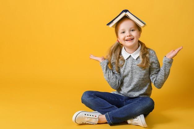 Маленькая студенческая девушка сидит с книгой на голове. Premium Фотографии