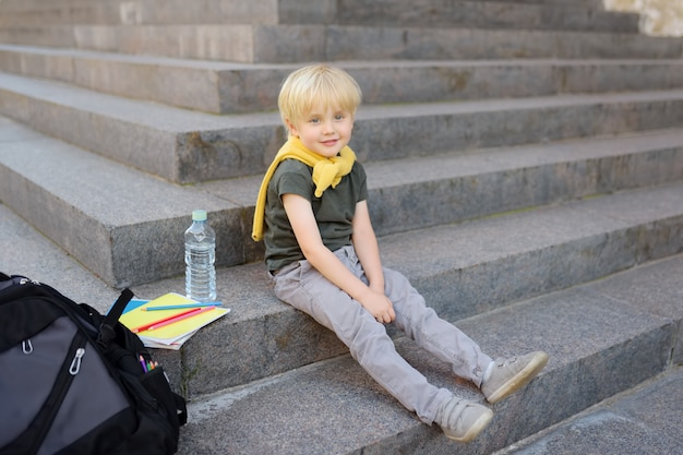 Little student sitting on staircase near the school building. Premium Photo