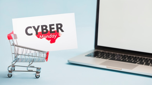 Little supermarket cart with big label and laptop Free Photo