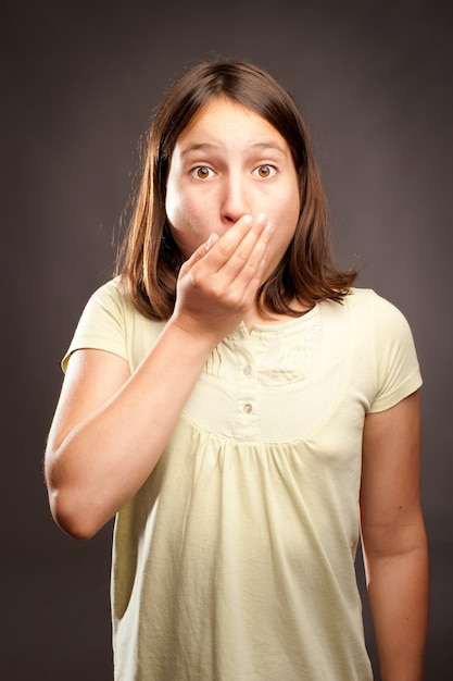 Little surprised girl covering mouth with her hand Premium Photo