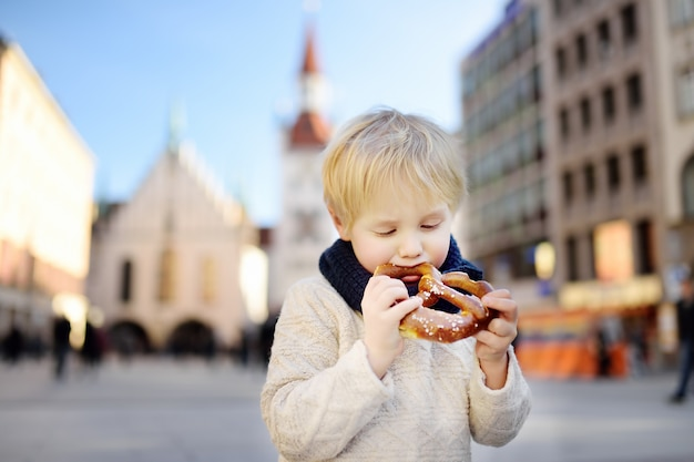 Little tourist holding traditional bavarian bread called pretzel on the town hall in munich, germany Premium Photo