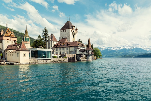 Little tower of oberhofen castle in the thun lake with mountains on background in switzerland Premium Photo