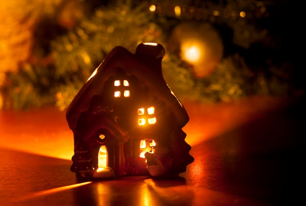 Little toy christmas house with a burning light inside Premium Photo