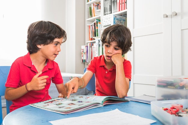 Little twins discussing book Free Photo