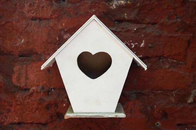 赤レンガの壁からぶら下がっているハートのシンボルの穴と小さな白い巣箱。愛の鳥の家、バレンタインギフトの概念 Premium写真