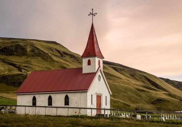 Vik 아이슬란드의 빨간 지붕 Reyniskyrka가있는 작은 흰색 교회 무료 사진