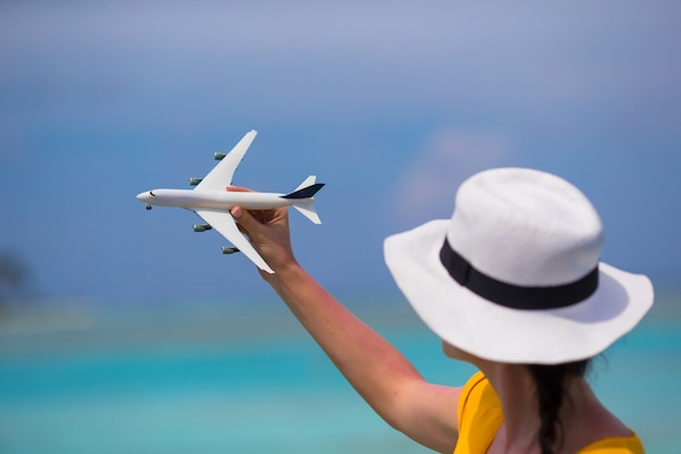 Little white toy airplane on background of turquoise sea Premium Photo