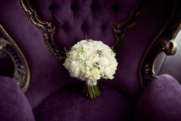 Little white wedding bouquet stands on violet chair Free Photo