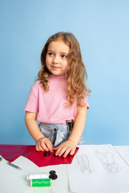Little woman dreaming about future profession of seamstress Free Photo