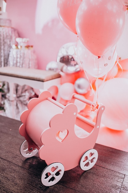 Little wooden baby stroller toy at a baby shower party Free Photo