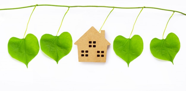 Little wooden house with green leaves heart shaped on white Premium Photo