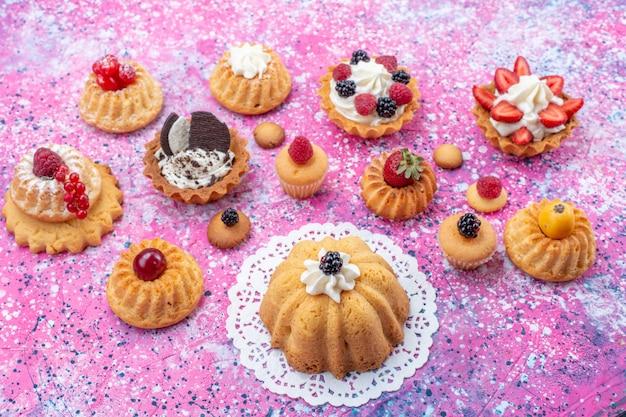 Маленькие вкусные лепешки со сливками и разными ягодами на светло-ярком, бисквитном ягодном сладком чае Бесплатные Фотографии