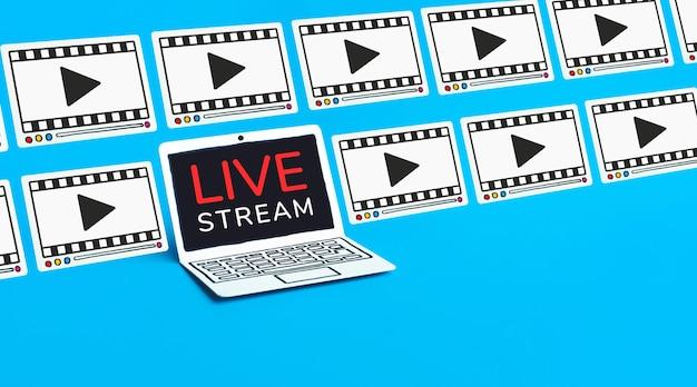青色の背景のラップトップでライブストリーミングテキスト Premium写真