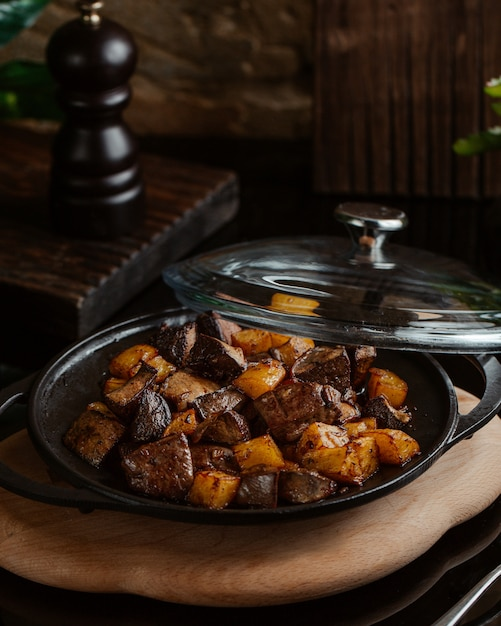 Liver grilled with square cut potatoes in black sac plate Free Photo