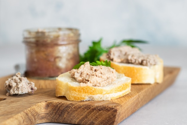 Liver pate in a glass jar with fresh bread and parsley on a wooden cutting board. Premium Photo