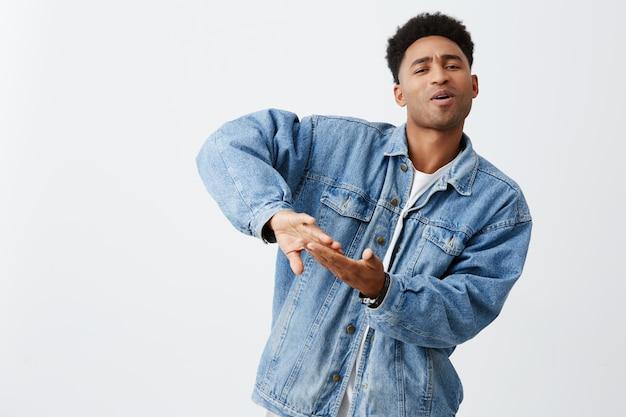 Жить богатой жизнью. позитивные эмоции. портрет молодого привлекательного чернокожего мужчины с афро прической в белой футболке и джинсовой куртке, выбрасывающих деньги на видеоклип, развлекающихся с друзьями Бесплатные Фотографии