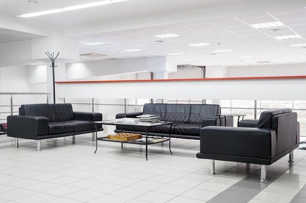 Интерьер гостиной для ресепшн с черными кожаными диванами ручной работы с белым рисунком на стенах, потолках, полу. прием для гостей в офисе Premium Фотографии