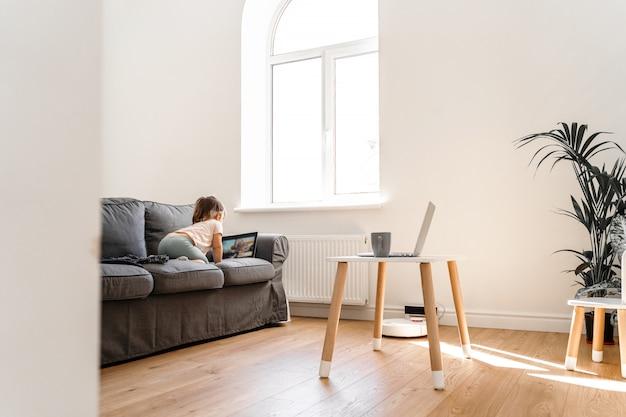 Гостиная с ребенком, смотрящим мультфильмы на диване и в родительском офисе Premium Фотографии