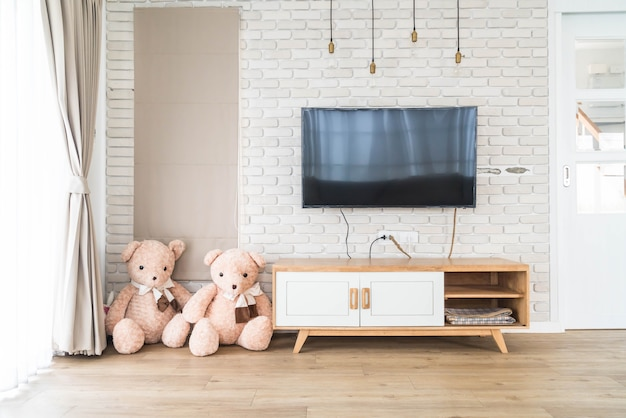 Living room with led tv on brick wall and wooden table Premium Photo