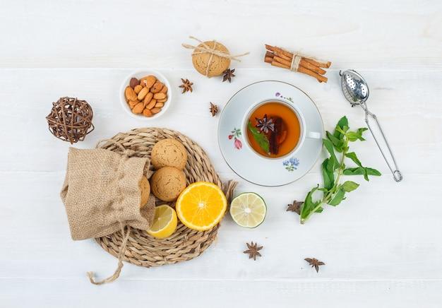 Llimes e biscotti su tovaglietta rotonda con una tazza di tè, una ciotola di mandorle e un colino da tè Foto Gratuite