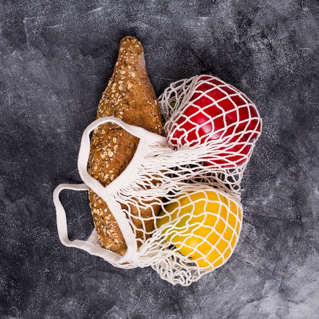 Loaf of bread; red and yellow bell pepper in white net bag on textured backdrop Free Photo