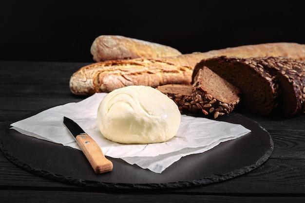 Буханка хлеба с маслом и ножом. темный фон, вид сбоку. Premium Фотографии