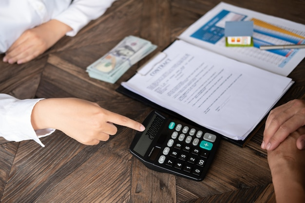 Loan repayment calculator woman bank employee showing calculator to house owner for loan r Premium Photo