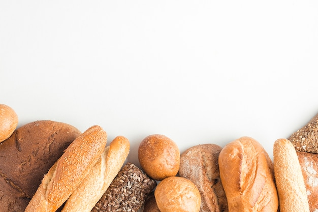 Loaves of baked breads on white backdrop Free Photo