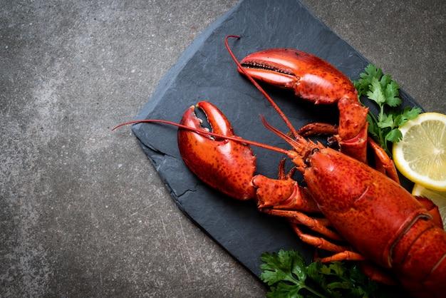 Lobster with vegetable and lemon on black slate plate Premium Photo