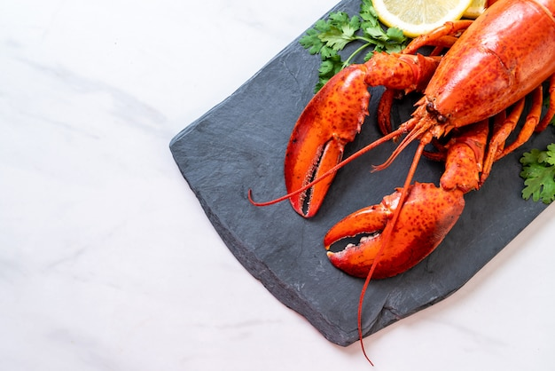 Lobster with vegetable and lemon on black slate plate Premium Photo