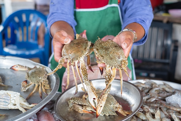 Local seafood seller hold and show two grabs. local seafood shop in thailand. Premium Photo