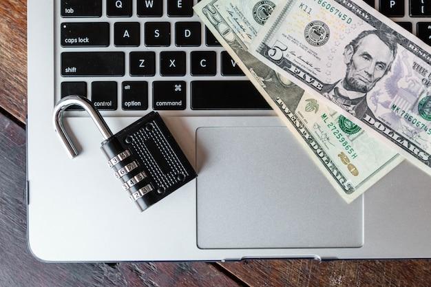 Locker and dollars on a laptop. transactions online idea. Premium Photo