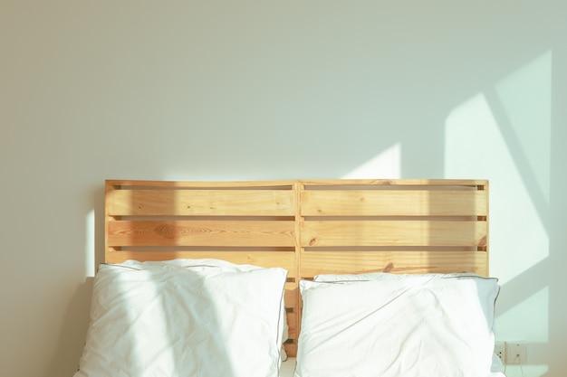 Спальня-лофт с белой кроватью в мягком солнечном свете зимнего утра. Premium Фотографии