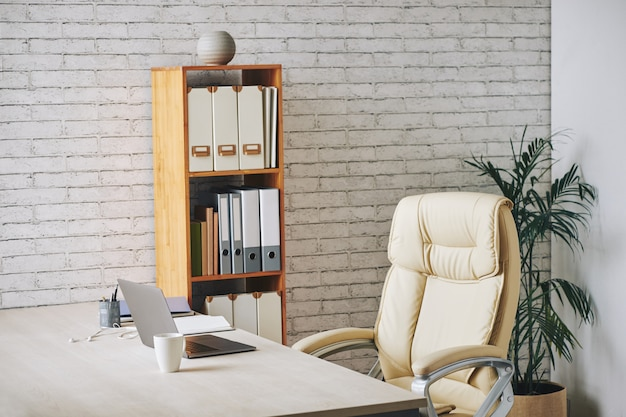 Loft-style office with laptop sitting on desk, executive chair and document folders on shelves Free Photo
