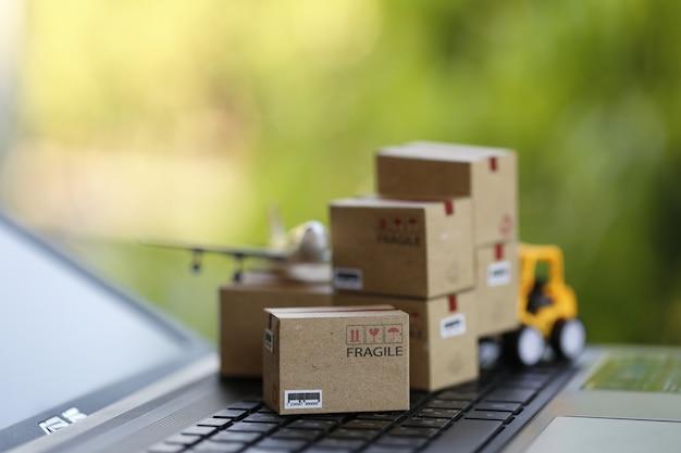 Концепция логистики и перевозки груза: автопогрузчик двигает бумажную коробку на клавиатуре тетради в естественной зеленой природе. изображает международную службу доставки или доставки для покупок в интернете. Premium Фотографии