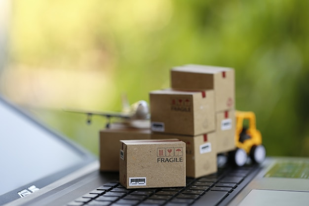 Logistic and cargo freight concept: fork-lift a truck moves a paper box on notebook keyboard in the natural green nature. depicts  international freight or shipping service for online shopping. Premium Photo
