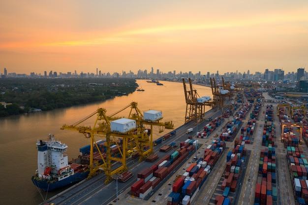 コンテナ貨物船と貨物飛行機の物流と輸送、日の出造船所のクレーン橋の作業、物流輸入輸出と輸送業界の背景 Premium写真