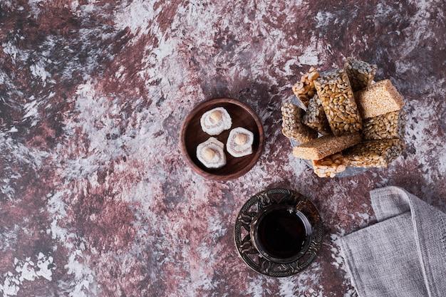Лукум и кунжутное печенье с стаканом чая, вид сверху Бесплатные Фотографии