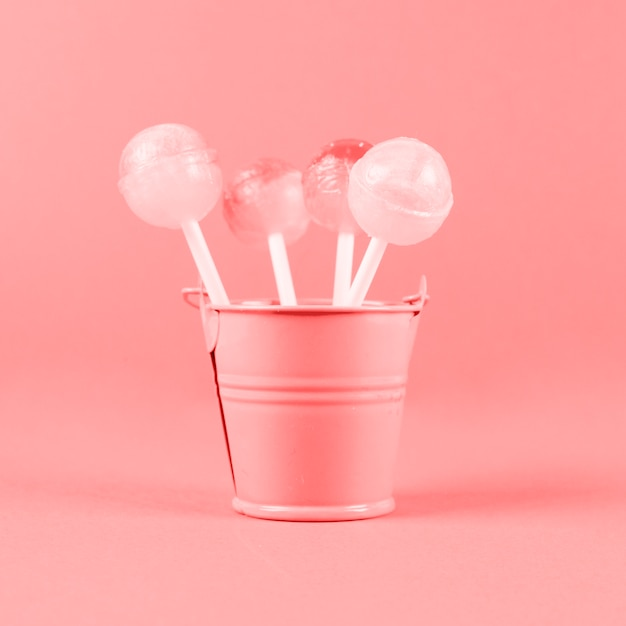 Lollipops in the small painted bucket against coral background Free Photo