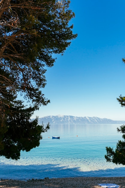 A lone boat floating on lake with mountain in distance against blue clear sky Free Photo