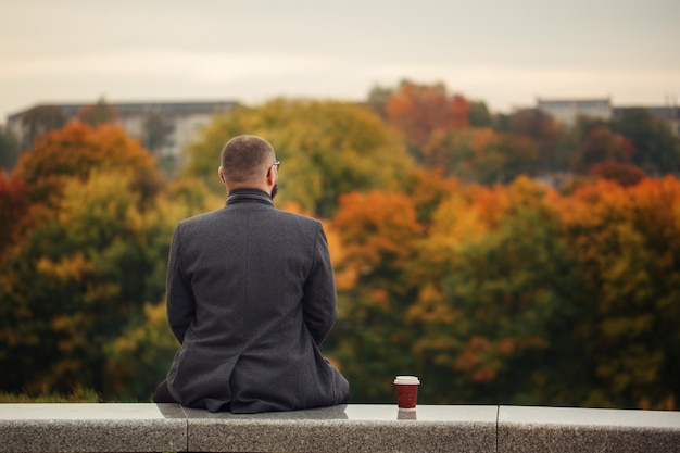 Lone man sitting on the stone bench and looking at nature. Premium Photo