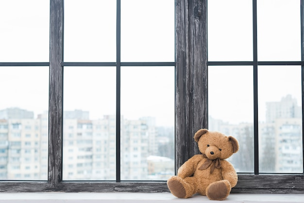 Lone teddy bear sitting near the closed window sill Free Photo