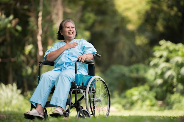 Lonely elderly woman sitting sad feeling on wheelchair at garden in hospital Free Photo