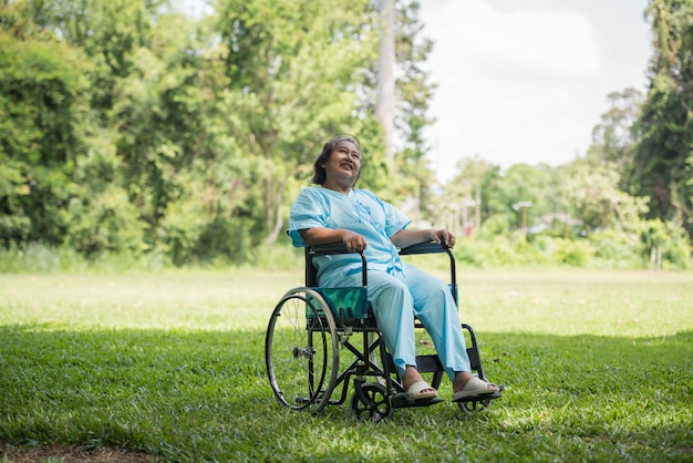 Lonely elderly woman sitting on wheelchair at garden in hospital Free Photo